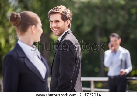 Three happy business partner people talking outside. brunette girl looking at man and smiling outside