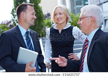 Three happy business people doing small talk outside the office