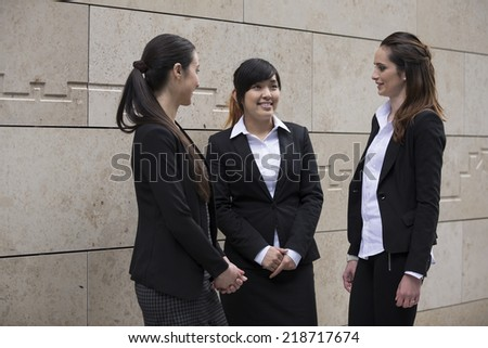 Three Happy Business women outside the office talking to each other. - stock photo