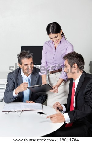 Three happy businesspeople in meeting at office - stock photo