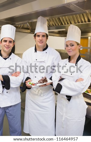 Three happy Chef's presenting a cake in the kitchen