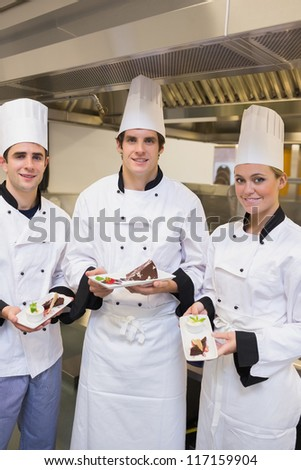 Three happy Chef's presenting cakes in the kitchen