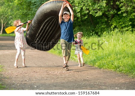 Three happy children carry a rubber boat with oars on a footpath in the forest - stock photo