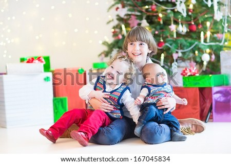 Three happy children - cute boy, his toddler sister and a newborn baby - sitting under a beautiful Christmas tree - stock photo