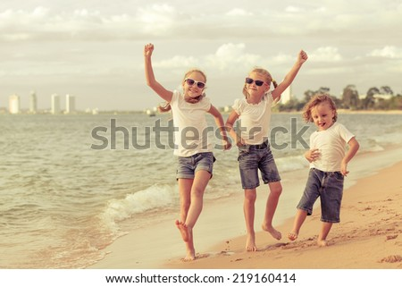 Three happy children dancing on the beach at the day time - stock photo