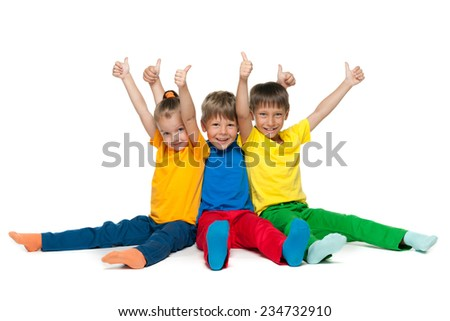 Three happy children hold their thumbs up on the white background - stock photo