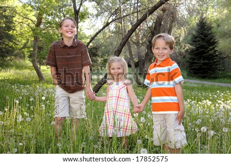 three happy children holding hands outdoors