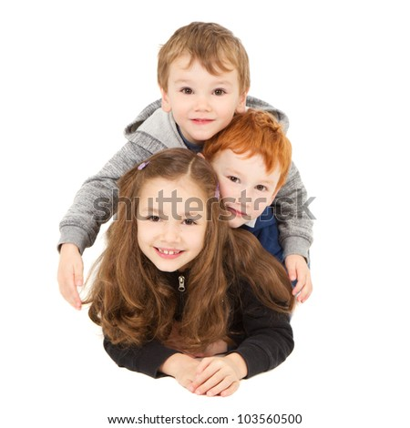Three happy children laying down in pile. Isolated on white. - stock photo