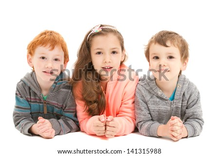 Three happy children laying on floor smiling. On white.