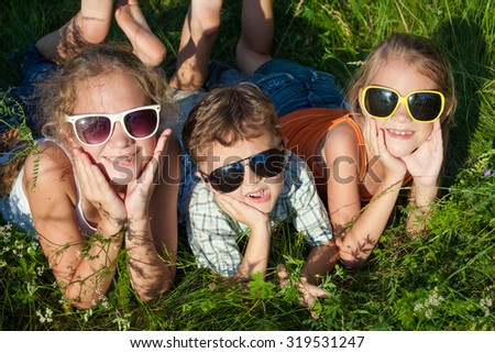 Three happy children  playing in the park at the day time. Concept Brother And Sister Together Forever