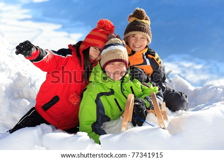 Three happy children playing on snowy mountain. - stock photo