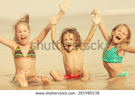 Three happy children  playing on the beach at the day time. - stock photo