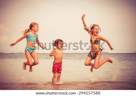 Three happy children  playing on the beach at the day time - stock photo
