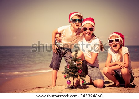 Three happy children  playing on the beach at the day time. Concept of Happy New Year. - stock photo