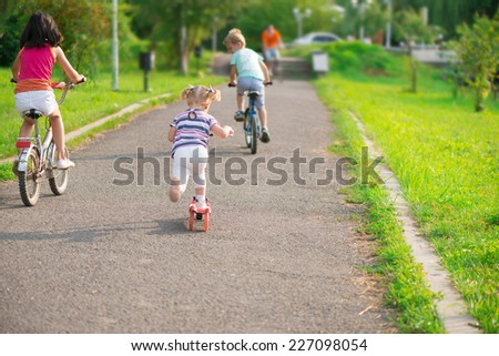 Three happy children riding on bicycle and scooter