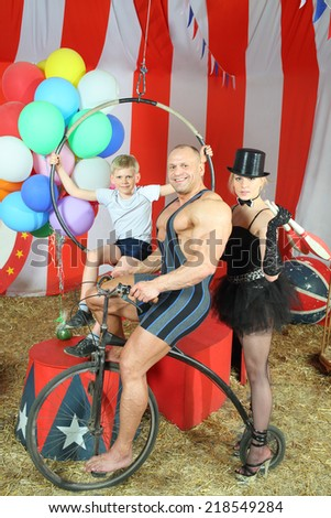 Three happy circus strong man, woman in cylinder and boy on retro bike with balloons in striped tent - stock photo