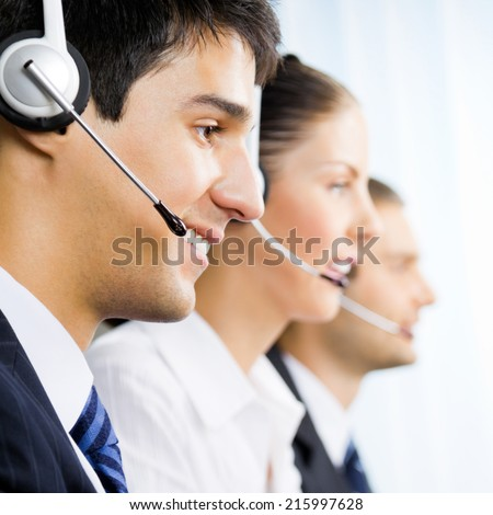 Three happy customer support phone operators, at workplace - stock photo
