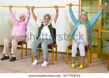 Three happy elderly ladies doing exercises in a seniors gym sitting in chairs raising wooden poles above their heads while smiling and laughing