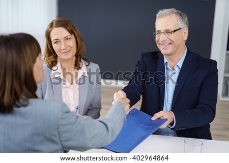 Three happy executives closing an important business transaction or negotiation and exchanging documents while sitting in office with copy space - stock photo