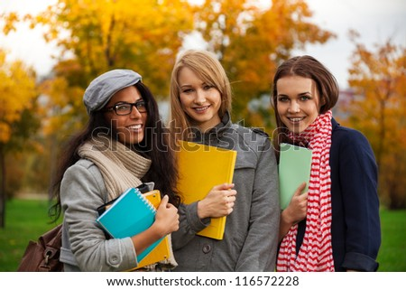 Three happy female students standing in autumn park - stock photo