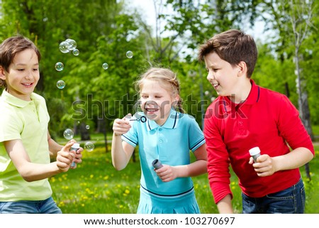 Three happy friends blowing soap bubbles outside