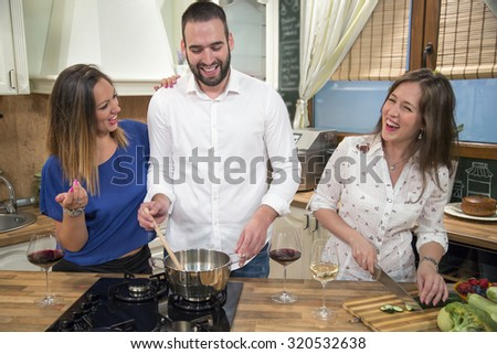 Three happy friends cooking and having fun in the kitchen. They are preparing food together and laughing. - stock photo