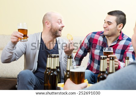 Three happy friends drinking beer and talking indoors - stock photo