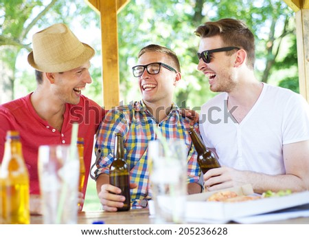 Three happy friends drinking beer, chatting and having fun in pub garden - stock photo