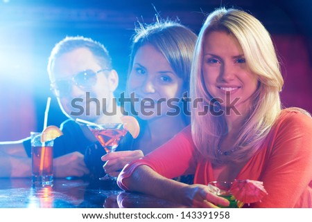 Three happy friends having party in bar, pretty blonde on foreground - stock photo
