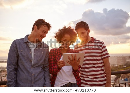 Three happy friends looking at the tablet joyously while the sun is setting behind them, wearing casual clothing