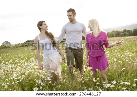 Three happy friends spending free time together in a field