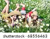 three happy friends teen girls laying on the daisy meadow - stock photo