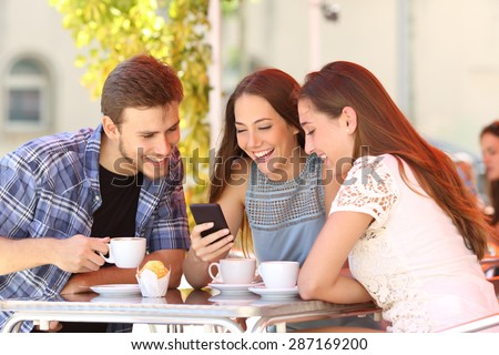 Three happy friends watching social media in a smart phone in a coffee shop - stock photo