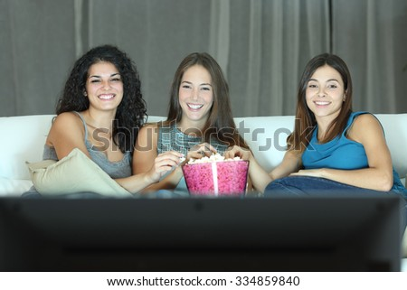 Three happy friends watching tv sitting on a couch at home - stock photo