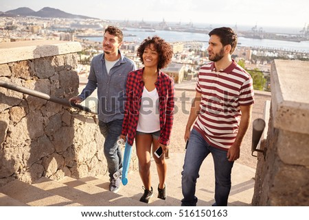 Three happy friends with a skateboard and cell phone walking up steps with big smiles with a city and bay in the background