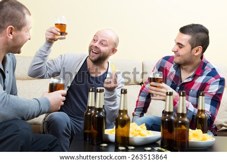Three happy friends 35-40 years old drinking beer and talking at home - stock photo