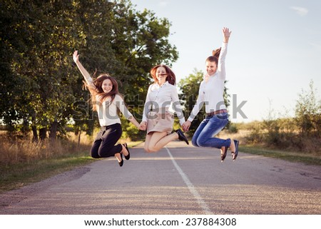 Three happy girls jumping on the road - stock photo