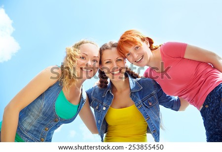 Three happy girls looking at camera and laughing. girls embracing.view  from below
