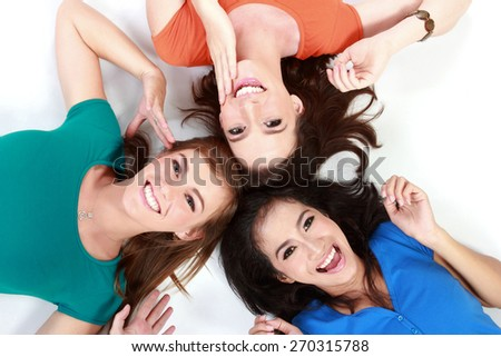 Three happy girls smiling lying on the floor - stock photo