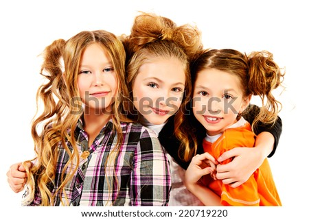 Three happy girls standing together and smiling. Isolated over white. - stock photo