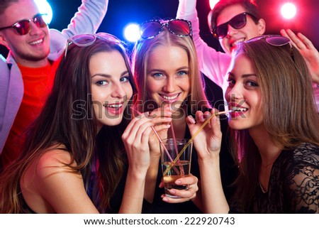 Three happy girls together drinking cocktails at a party