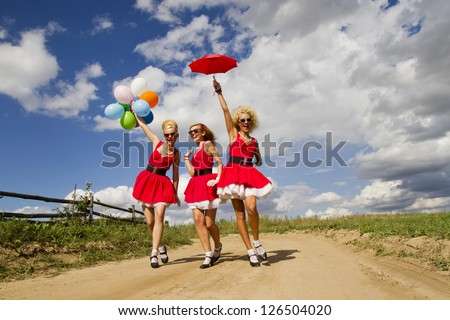 Three happy girls with balloon and umbrella in red dresses.