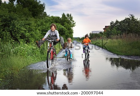 Three happy kids are going through a puddle - stock photo