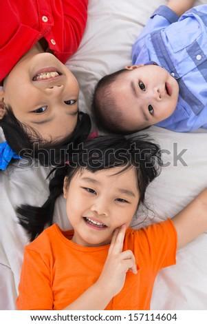 Three happy kids ,baby on the floor laying on - stock photo
