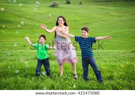 Three happy kids catch the soap bubbles on green lawn