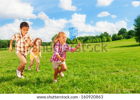 Three happy kids chasing with butterfly net in the park together, boys and girls