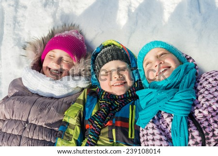 Three happy kids having fun in winter park - stock photo