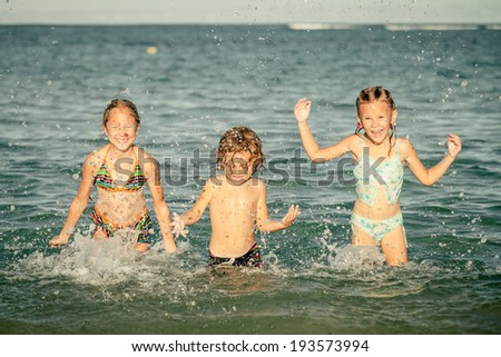 three happy kids playing on beach at the day time - stock photo
