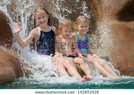 three happy kids sitting near the pool in the waterpark - stock photo