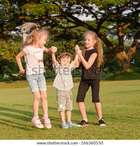 three happy little kids playing in the park in the day time - stock photo